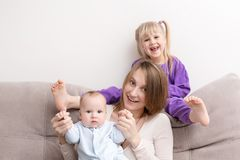 Mother with son and daughter having fun on sofa. Smiling and cheerful people. Happy family concept stock photo