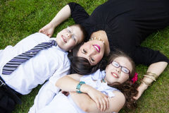 Mother with son and daughter laying in grass Stock Photos