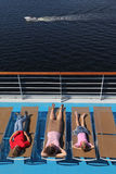 Mother, son and daughter lying at deck-chair. Top view of mother, son and little daughter lying at deck-chair on ship and looking at cutter Stock Photo