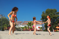 Mother with son and daughter plays on beach. Mother with her son and daughter plays in blindman's buff on beach Stock Image