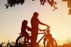 Mother with son and daughter riding bike at sunset Stock Image
