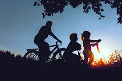 Mother with son and daughter riding bikes and scooter at sunset Royalty Free Stock Images