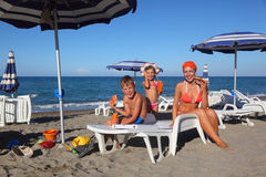 Mother, son and daughter sitting on beach Stock Images