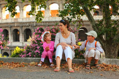 Mother, son and daughter sitting near Colosseum. Young mother, little son and daughter sitting near Colosseum in Rome and talking, focus on mother Royalty Free Stock Images