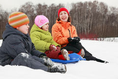 Mother, son and daughter sitting on snow Stock Image