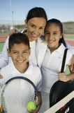 Mother, son and daughter on tennis court. Mother with son and daughter by net on tennis court, portrait Stock Photos