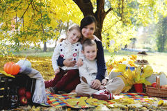 Mother with son and daughter under autumn trees Stock Photos