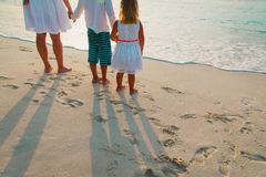 Mother with son and daughter walk on sand beach. At sunset Royalty Free Stock Image