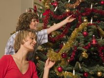 Mother and son decorating Christmas tree. Mother and son decorating a Christmas tree with red and gold royalty free stock image