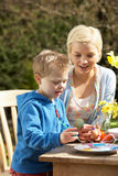 Mother And Son Decorating Easter Eggs. On Table Outdoors Stock Photo