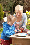 Mother And Son Decorating Easter Eggs. On Table Outdoors Royalty Free Stock Photography