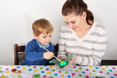 Mother And Son Decorating Easter Eggs On Table indoor. Mother And Son Decorating Easter Eggs On Table indoor Stock Image