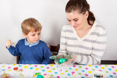 Mother And Son Decorating Easter Eggs On Table indoor. Mother And Son Decorating Easter Eggs On Table indoor Stock Photography