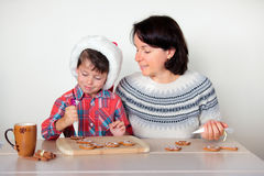 Mother and son decorating the gingerbread cookies Stock Photography
