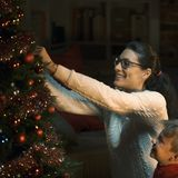Mother and son decorating their Christmas tree together royalty free stock photography