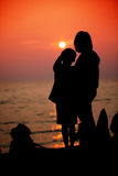Mother and son in a deep moment of love during sunset at beach. Concept of union and tender connection between a young mama and his lovely child Royalty Free Stock Images