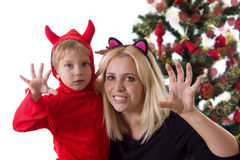 Mother and son in deuce costumes under Christmas tree stock photography