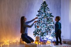 Mother and son dinner at Christmas Garland lights new year gifts. Mom with son decorate Christmas tree new year gifts Garland stock photography