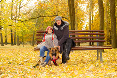Mother and son with dog in park. Sitting on the bench royalty free stock image