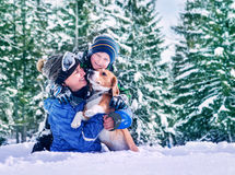 Mother with son and dog playing together in snow forest Stock Photography