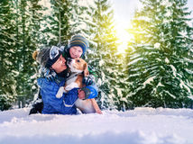 Mother with son and dog playing together in snow forest Stock Photo