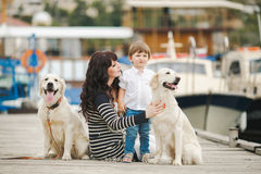 Mother and son with a dog sitting on the waterfront Royalty Free Stock Photography