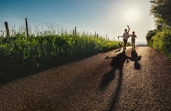 Mother, son and dog walk on country sunset road and make funny c Royalty Free Stock Images