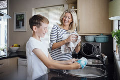 Mother and Son Doing the Dishes. Together. They are talking and laughing as the boy washes and the mother dries dishes Royalty Free Stock Photo