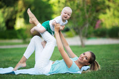 Mother and son doing exercise outdoors. Healthy lifestyle. Yoga Stock Photos