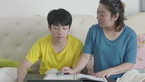 Mother with son doing homework in the bedroom. stock video footage
