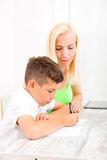 Mother and son doing homework. A mother helping his son with his homework Royalty Free Stock Photos