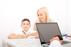 Mother and son doing homework. A mother helping his son with his homework Stock Photo