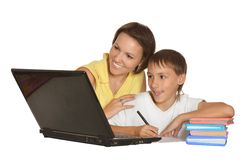 Mother and son doing homework with laptop Stock Photos