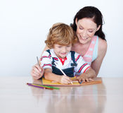 Mother and son doing homework together Stock Photos