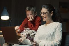 Mother and son doing online shopping together royalty free stock photography