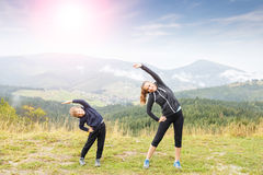Mother and son doing stretching in the mountains Stock Image
