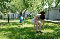 Mother and son doing yoga exercises on grass in the yard at the day time. People having fun outdoors Royalty Free Stock Photos