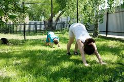 Mother and son doing yoga exercises on grass in the yard at the day time. People having fun outdoors Stock Photo
