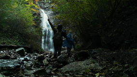 Mother with son done a long way to Waterfall stock video footage
