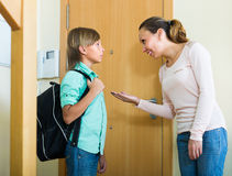 Mother with son at doorway. Smiling mother gives moral admonitions to son at doorway stock image