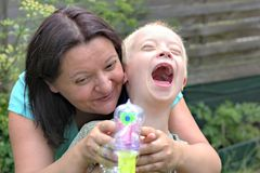 Mother and son with down syndrome. Defect,childcare,medicine and people concept- happy mother and son with down syndrome playing in a garden Royalty Free Stock Photo