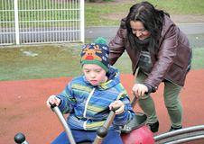 Mother and son with down syndrome. Defect,childcare,medicine and people concept- happy mother and son with down syndrome playing in a garden Royalty Free Stock Image