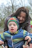 Mother and son with down syndrome. Defect,childcare,medicine and people concept- happy mother and son with down syndrome playing in a playground Royalty Free Stock Photos