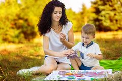 Mother and son draw. Concept of happy family. Mother and son draw outdoor. Concept of happy family stock photos