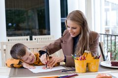 Mom helps son to draw drawing colored pencils. Mother and son draw drawing hands colored pencils Stock Photos