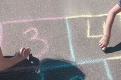 Mother and son draw numbers two and three on the hopscotch on asphalt. Mother and son draw numbers two and three on the hopscotch on asphalt royalty free stock images