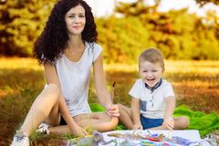 Mother and son draw. Concept of happy family. Mother and son draw outdoor. Concept of happy family stock images