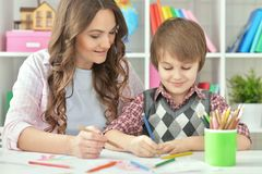 Mother and son drawing. Mather and her little son drawing with colorful pencils Stock Photo
