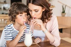 Mother and son drinking milkshake together. In cafe Royalty Free Stock Images