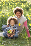 Mother And Son On Easter Egg Hunt. In Daffodil Field Smiling royalty free stock photography